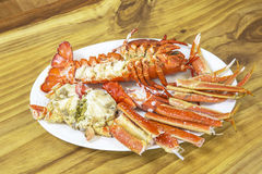 Cooked lobster on white dish. With wooden texture background Royalty Free Stock Image