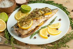 Cooked mackerel on a white plate with spices, herbs, lemon, lime and salt. A close-up, on a wooden background.Concept of homemade. Food, and tasty healthy food stock photos