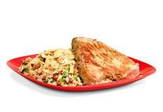 Cooked meal of brown rice and beans with a tuna fish steak on a red plate Royalty Free Stock Photography