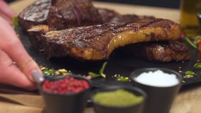 Cooked meat, appetizing ribs and medallions are served on a tray. HD stock video footage