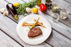 Cooked meat and raw vegetables. Eggplant and rosemary. Ribeye steak with thyme. Tasty food cooked at bistro Stock Photography