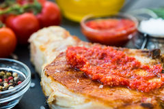 Cooked meat with red sauce, garlic, cherry tomatoes, olive oil Royalty Free Stock Images