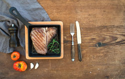 Cooked meat t-bone steak with garlic cloves, tomatoes, rosemary, pepper and salt in small cooking pan over rustic wooden Stock Images