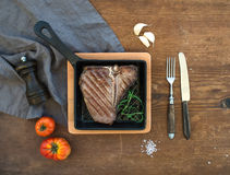 Cooked meat t-bone steak with garlic cloves, tomatoes, rosemary, pepper and salt in small cooking pan over rustic wooden Stock Image