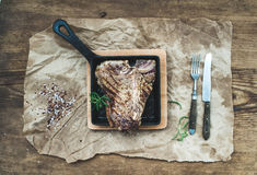 Cooked meat t-bone steak in grilling pan with spices and fresh rosemary on oily craft paper over rustic wooden. Cooked meat t-bone steak in grilling pan with Stock Image