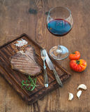 Cooked meat t-bone steak on serving board with garlic cloves, tomatoes, rosemary, spices and glass of red wine over Stock Images