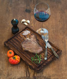 Cooked meat t-bone steak on serving board with garlic cloves, tomatoes, rosemary, spices and glass of red wine over Stock Image