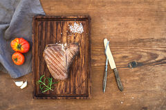 Cooked meat t-bone steak on serving board with garlic cloves, tomatoes, rosemary and spices over rustic wooden Royalty Free Stock Photo