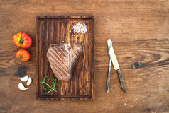 Cooked meat t-bone steak on serving board with garlic cloves, tomatoes, rosemary and spices over rustic wooden Royalty Free Stock Image