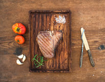 Cooked meat t-bone steak on serving board with garlic cloves, tomatoes, rosemary and spices over rustic wooden Stock Photo