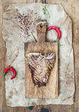 Cooked meat t-bone steak on serving board with red chili peppers, spices, fresh rosemary over oily craft paper and Stock Photos
