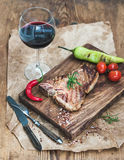 Cooked meat t-bone steak on serving board with roasted tomatoes, charlestone green pepper, chili, fresh rosemary, spices Stock Photography