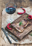 Cooked meat t-bone steak on serving board with roasted tomatoes, chili peppers, fresh rosemary, spices and glass of red Stock Photo