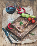 Cooked meat t-bone steak on serving board with roasted tomatoes, chili peppers, fresh rosemary, spices and glass of red Stock Images