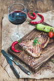 Cooked meat t-bone steak on serving board with roasted tomatoes, chili peppers, fresh rosemary, spices and glass of red Royalty Free Stock Photography