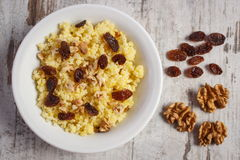 Cooked millet groats with raisins and walnuts on white plate, healthy food and nutrition Royalty Free Stock Images