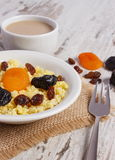 Cooked millet groats on white plate and cup of coffee with milk, healthy food and nutrition Stock Photos