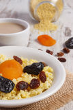 Cooked millet groats on white plate and cup of coffee with milk, healthy food and nutrition Stock Photography