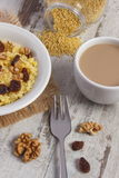 Cooked millet groats on white plate and cup of coffee with milk, healthy food and nutrition Stock Images