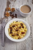 Cooked millet groats on white plate and cup of coffee with milk, healthy food and nutrition Stock Image