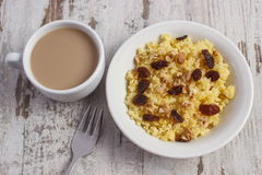 Cooked millet groats on white plate and cup of coffee with milk, healthy food and nutrition Royalty Free Stock Image