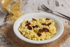 Cooked millet groats on white plate, healthy food and nutrition Stock Photography