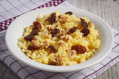 Cooked millet groats on white plate, healthy food and nutrition Stock Photo