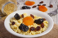 Cooked millet groats on white plate, healthy food and nutrition. Fresh cooked millet groats with raisins, dried apricot and plum on white plate, concept of Royalty Free Stock Photos