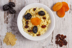 Cooked millet groats on white plate, healthy food and nutrition Royalty Free Stock Photos