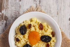 Cooked millet groats on white plate, healthy food and nutrition. Cooked millet groats with raisins, dried apricot and plum on white plate, concept of healthy Royalty Free Stock Images