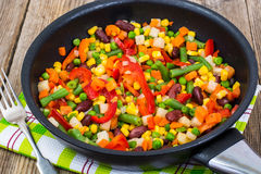 Cooked mixed vegetables in frying pan on wooden table. Studio Photo Stock Photos