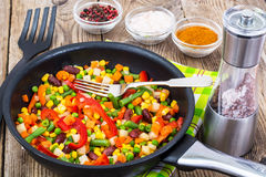 Cooked mixed vegetables in frying pan on wooden table. Studio Photo Stock Images