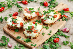 Cooked Mushrooms stuffed with cheese and plum tomatoes. Stock Photos