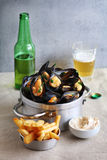 Cooked mussels in an aluminum pan with french fries Stock Photo