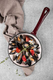 Cooked mussels in a pan served on a napkin garnished with tomatoes and thyme. Steamed mussels in white wine sauce. Seafood mussels on pan with cream sauce. Top Royalty Free Stock Photography