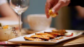 Cooked mussels served on a plate. A man squeezes lemon juice on top of it. Mid shot stock footage