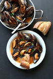 Cooked mussels in tomato sauce garnished with parsley Stock Photo