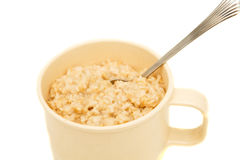 Cooked Oatmeal in a Cup with Spoon Stock Images