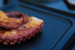 Cooked Octopus Plate with lime in black stone background Royalty Free Stock Image