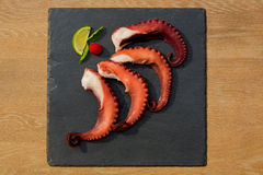 Cooked Octopus Plate with lime in black stone background Stock Images