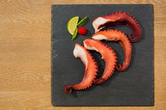 Cooked Octopus Plate with lime in black stone background Royalty Free Stock Photos