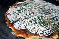Cooked Okonomiyaki on hotplate. A closeup of a cooked Okonomiyaki (Japanese cabbage pancake) on a hotplate. It is topped with Okonomiyaki sauce, seaweed flakes stock images