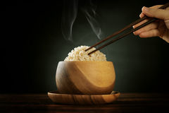 Cooked organic basmati brown rice with steam and chopsticks Royalty Free Stock Image