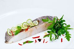 Cooked organic slice of white fish fillet seafood with fresh arugula leaves salad and lemon lime slices