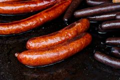 Paprika bratwurst sausages on cast iron griddle. Royalty Free Stock Photo