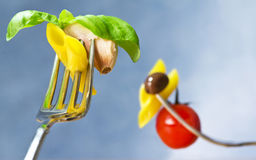Cooked pasta on fork with ingredients Stock Photo