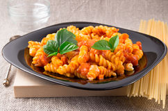 Cooked pasta girandole on a black plate Royalty Free Stock Images