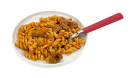 Cooked pasta and sausage on plate with fork Royalty Free Stock Image