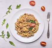 Cooked pasta with turkey and onions, tomatoes arugula on a white plate with a fork on wooden rustic background top view stock photography