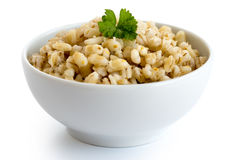 Cooked pearl barley with green parsley in white ceramic bowl iso Royalty Free Stock Image